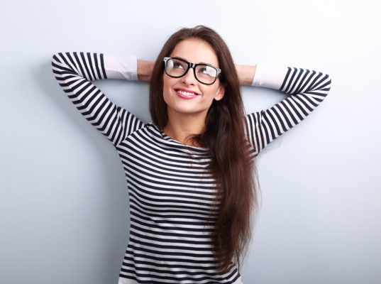 47917116 - beautiful relaxing woman in glasses looking up with thinking look on blue background with empty copy space